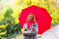 Молодая красивая женщина при зонтик представляя снаружи на времени падения Стоковая Фотография
