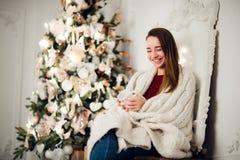 Молодая красивая женщина при сидя дом держа чашку горячего кофе нося связанный теплый свитер рождество моя версия вектора вала по Стоковые Фотографии RF