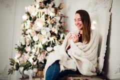 Молодая красивая женщина при сидя дом держа чашку горячего кофе нося связанный теплый свитер рождество моя версия вектора вала по Стоковые Изображения