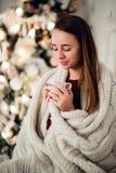Молодая красивая женщина при сидя дом держа чашку горячего кофе нося связанный теплый свитер рождество моя версия вектора вала по Стоковое фото RF