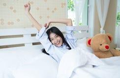 Молодая красивая женщина протягивая в кровати после бодрствования вверх, она усмехается Стоковое фото RF
