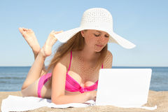 Молодая красивая женщина работая на белой компьтер-книжке на пляже Стоковые Фото