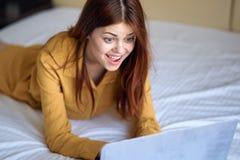 Молодая красивая женщина работая на компьютере дома в спальне, эмоциях Стоковое Фото