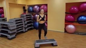 Молодая красивая женщина разрабатывая с stepper в спортзале акции видеоматериалы