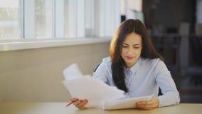 Молодая красивая женщина рассматривает различные документы в офисе сток-видео