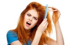 Молодая красивая женщина расчесывая ее волосы на белизне изолировала предпосылку, портрет, эмоцию стоковое фото rf