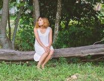 Молодая красивая женщина сидя на деревянном стенде и настолько сиротливая стоковое изображение
