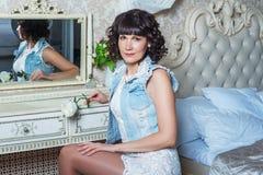 Молодая красивая женщина сидя на зеркале в спальне с таблицей шлихты Стоковое фото RF