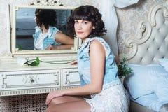 Молодая красивая женщина сидя на зеркале в спальне с таблицей шлихты Стоковые Изображения