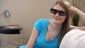Молодая красивая женщина сидя на кресле в 3d-glasses Смотрит кино 3d, чем переключатели с умного ТВ акции видеоматериалы
