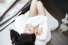 Молодая красивая женщина сидя на кресле на ее комнате Стоковое фото RF