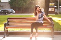 Молодая красивая женщина сидя на стенде и говоря на pho Стоковые Изображения RF