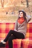 Молодая красивая женщина сидя на стенде и усмехаться Стоковые Фото