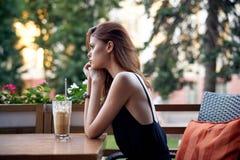 Молодая красивая женщина сидя на таблице в кафе на улице Стоковое Фото