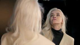 Молодая красивая женщина смотрит отражение белокурая модель способа привлекательный студент девушки видеоматериал