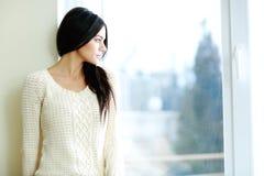 Молодая красивая женщина смотря окно Стоковые Изображения