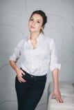 Молодая красивая женщина стоя против белизны Стоковые Изображения