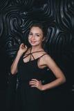 Молодая красивая женщина стоя против черноты Стоковое Фото