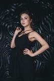 Молодая красивая женщина стоя против черноты Стоковые Изображения