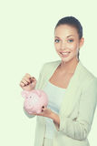 Молодая красивая женщина стоя с денежным ящиком копилки, на белой предпосылке Стоковые Изображения RF