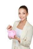 Молодая красивая женщина стоя с денежным ящиком копилки, на белой предпосылке Стоковое фото RF