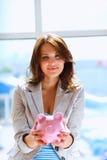 Молодая красивая женщина стоя с денежным ящиком копилки, на здании Стоковое Изображение RF