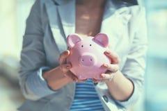 Молодая красивая женщина стоя с денежным ящиком копилки, на здании Стоковая Фотография RF