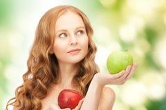 Молодая красивая женщина с зелеными и красными яблоками Стоковое Фото