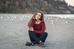 молодая красивая женщина с длинными волосами, в черных джинсах и красной рубашке, сидя на песке на пляже среди птиц чайок Стоковая Фотография