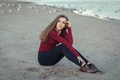 молодая красивая женщина с длинными волосами, в черных джинсах и красной рубашке, сидя на песке на пляже среди птиц чайок Стоковые Изображения RF