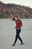 молодая красивая женщина с длинными волосами, в черных джинсах и красной рубашке, сидя на песке на пляже среди птиц чайок Стоковое Изображение RF