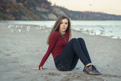 молодая красивая женщина с длинными волосами, в черных джинсах и красной рубашке, сидя на песке на пляже среди птиц чайок Стоковые Фото