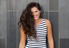 Молодая красивая женщина с длинными волосами усмехаясь против серой предпосылки стоковая фотография