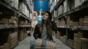 Молодая красивая женщина с тележкой полной товаров идя через высокие полки с вещами для ремонта в большом складе акции видеоматериалы