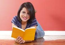 Молодая красивая женщина усмехаясь держащ книгу стоковое изображение