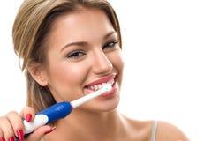 Молодая красивая женщина чистя ее здоровые зубы щеткой Стоковое Изображение RF