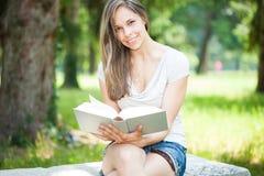 Молодая красивая женщина читая книгу в парке стоковое фото rf