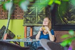 Молодая красивая женщина redhead сидя в кафе выпивая очень вкусный чай имбиря утра в кафе стоковые фото