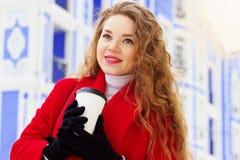 Молодая, красивая и стильная девушка белокурых волос в кофе красного пальто выпивая на улице города Мода женщин Стоковое Изображение