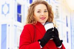 Молодая, красивая и стильная девушка белокурых волос в кофе красного пальто выпивая на улице города Мода женщин Стоковые Изображения