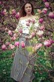 Молодая красивая кавказская женщина в зацветая саде весны магнолий Девушка в саде на пасмурный день Стоковое Изображение