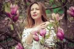 Молодая красивая кавказская женщина в зацветая саде весны магнолий Девушка в саде на пасмурный день Стоковое фото RF