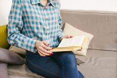 молодая красивая книга чтения девушки сидя на софе в комнате Стоковое Изображение
