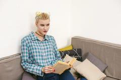 молодая красивая книга чтения девушки сидя на софе в комнате Стоковые Изображения RF