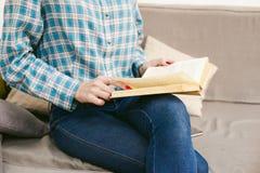 молодая красивая книга чтения девушки сидя на софе в комнате Стоковое Изображение RF