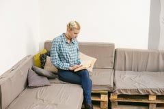 молодая красивая книга чтения девушки сидя на софе в комнате Стоковая Фотография