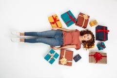 Молодая красивая курчавая девушка лежа на поле среди подарочных коробок сняла сверху изолированный Стоковая Фотография RF