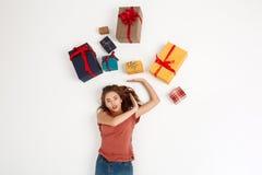 Молодая красивая курчавая девушка лежа среди подарочных коробок сняла сверху изолированный Стоковые Изображения