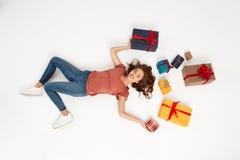 Молодая красивая курчавая девушка лежа среди подарочных коробок сняла сверху изолированный Стоковые Фотографии RF