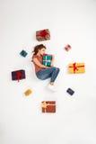 Молодая красивая курчавая девушка лежа среди подарочных коробок сняла сверху изолированный Стоковое фото RF